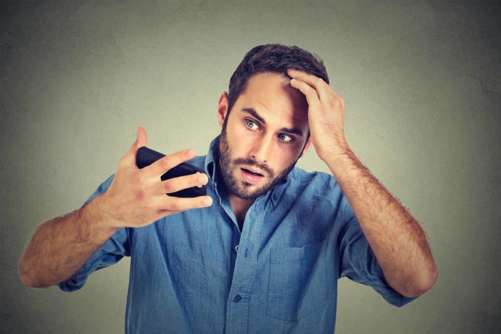 mężczyzna martwi się wypadaniem włosów i zakolami