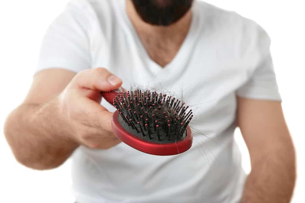 mężczyzna trzymający w ręce szczotkę pełną wypadających włosów