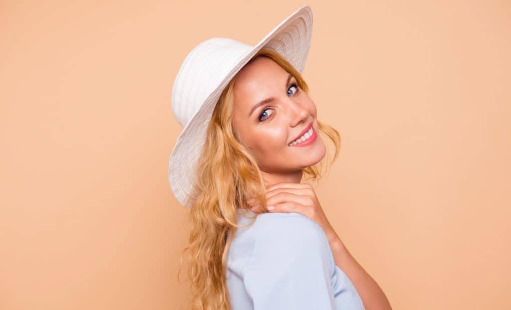 uśmiechnięta kobieta w kapeluszu z długimi włosami